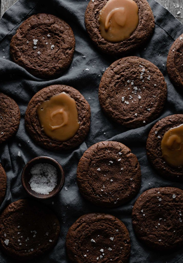 Salt and caramel topped chocolate cookies on blue linen.