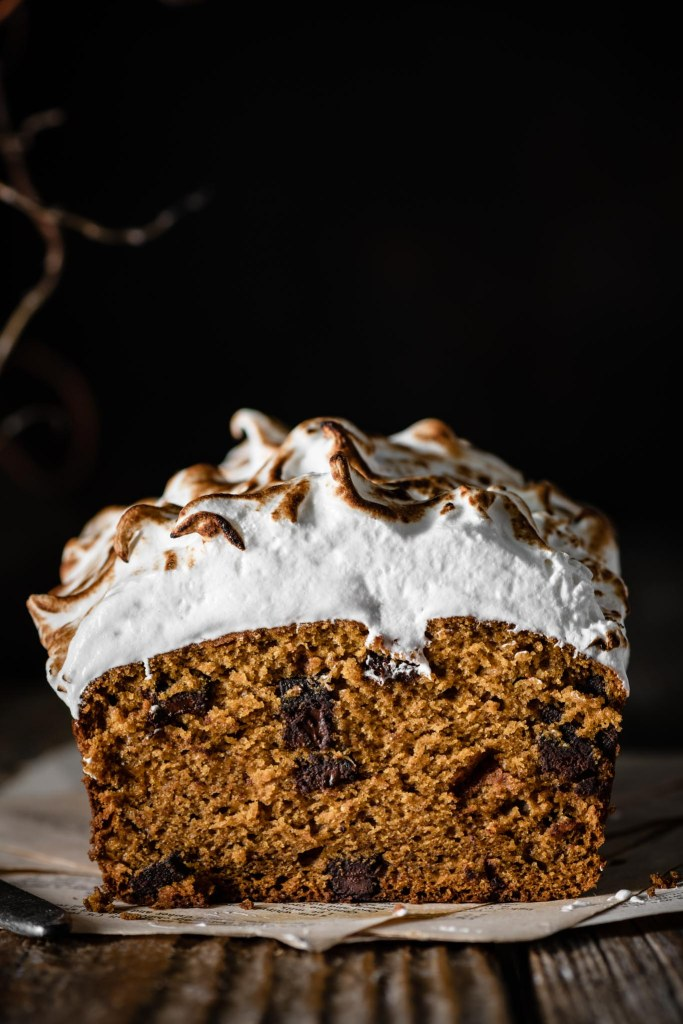 Pumpkin bread sliced showing chocolate chunks and toasted meringue topping.