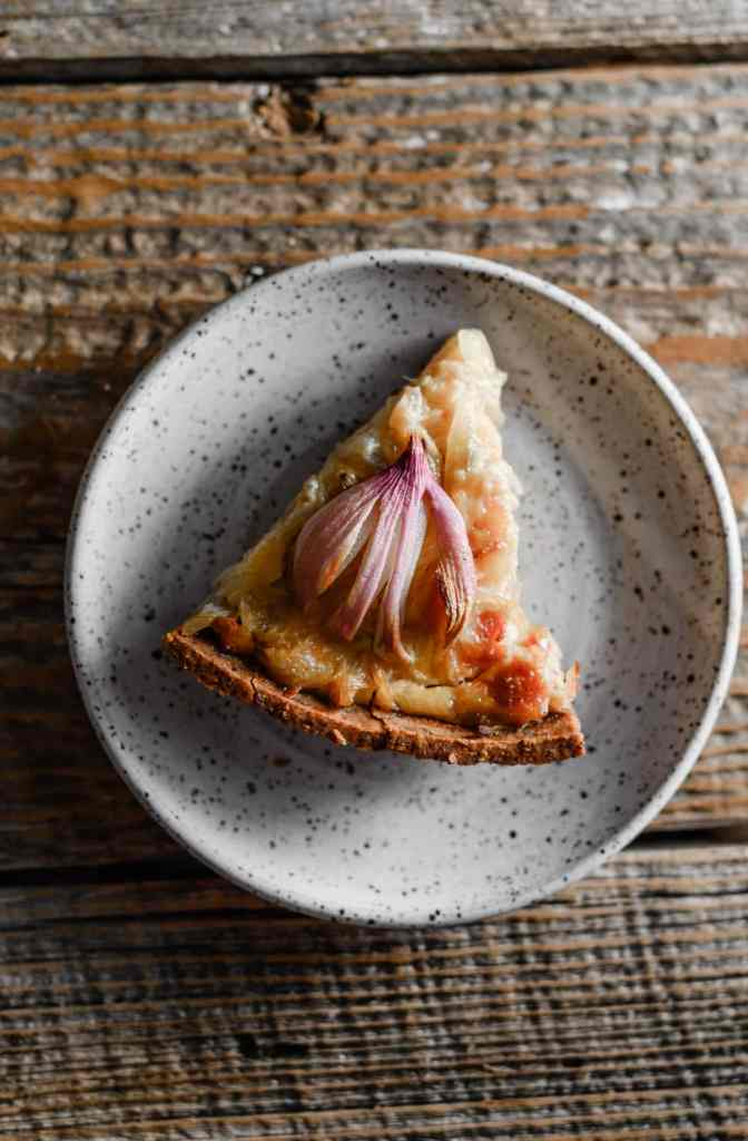 Slice of onion tart on a white plate.