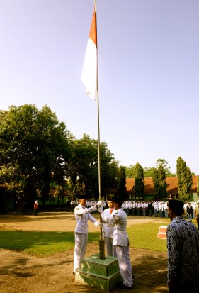 The flag is raised as everyone sings the national anthem, Indonesia Raya.