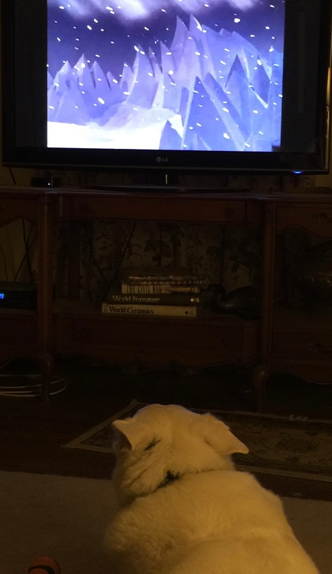 Yuki sits and watches Rudolf the Red Nosed Reindeer on TV