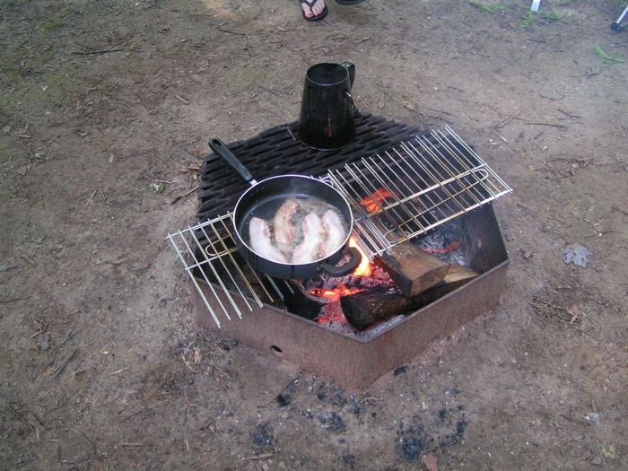 Cooking bacon over campfire for first camping trip breakfast