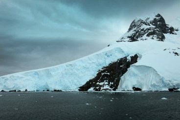 The rugged landscape is covered in a blanket of massive glaciers that reach up into the clouds.