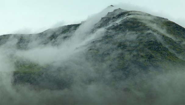 Fingers of clouds creep between the snow fences atop a mountain overlooking Siglufjordur.