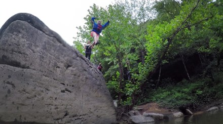 """Taking the leap off of """"Jump Rock"""" along the Cumberland."""