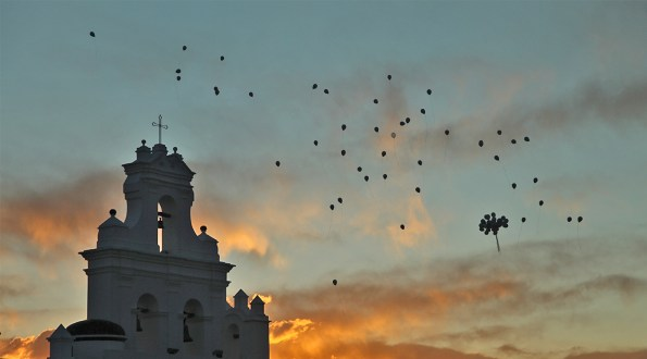 Balloons rise into the evening sky above Sucre.