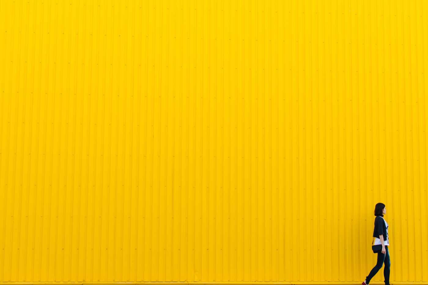 malutka sylwetka idącej kobiety na tle żółtego budynku
