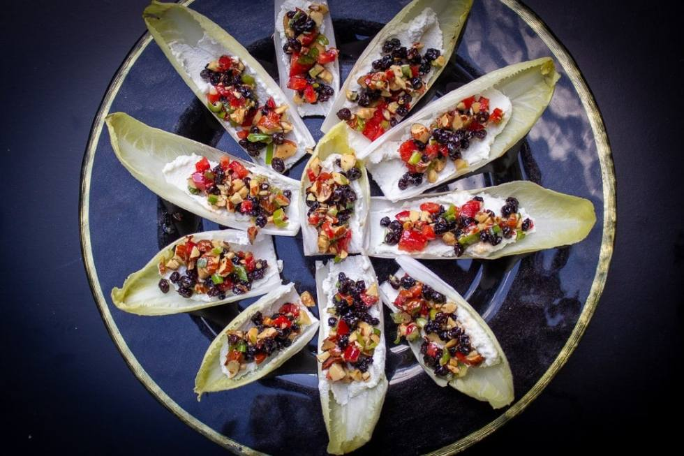Loaded Endive Ricotta Appetizer filled with currants, chives, peppers, almonds and drizzled with honey or balsamic reduction