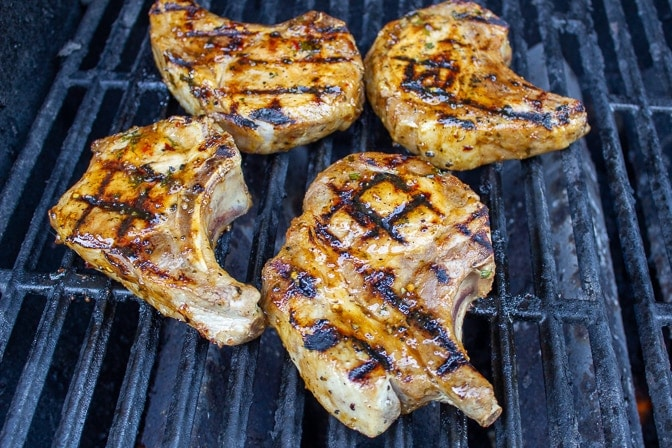 4 pork chops on grill with marinade glaze on top