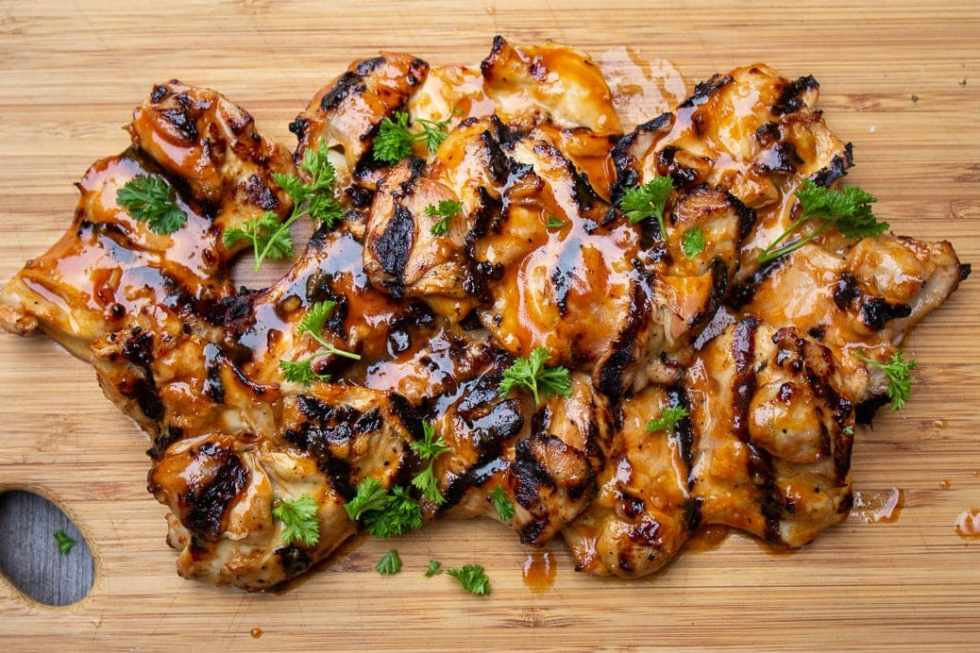 Grilled BBQ boneless Chicken thighs on cutting board