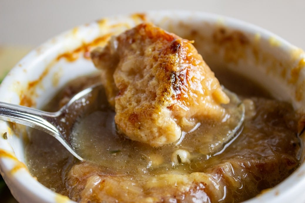 spoonful of onion soup with bread and cheese