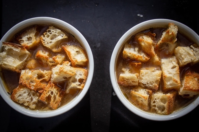 onion soup in bowls with toasted bread cubes