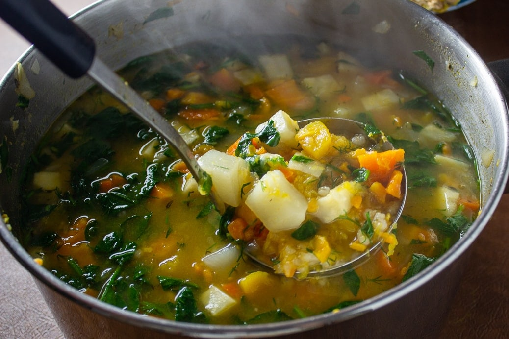 finished root vegetable soup with spinach and dill added, showing veggies on a ladle over pot