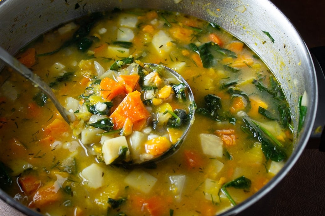 ladle full of root vegetable soup with Barley in pot