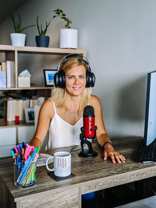 kobieta siedząca przy biurku z mikrofonem