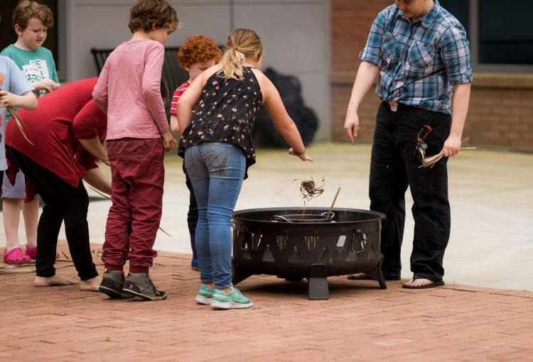 Two Rivers kids burning palm branches to make ashes for Ash Wednesday