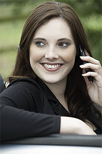 Corporate head shot of a female model with a telephone in a car