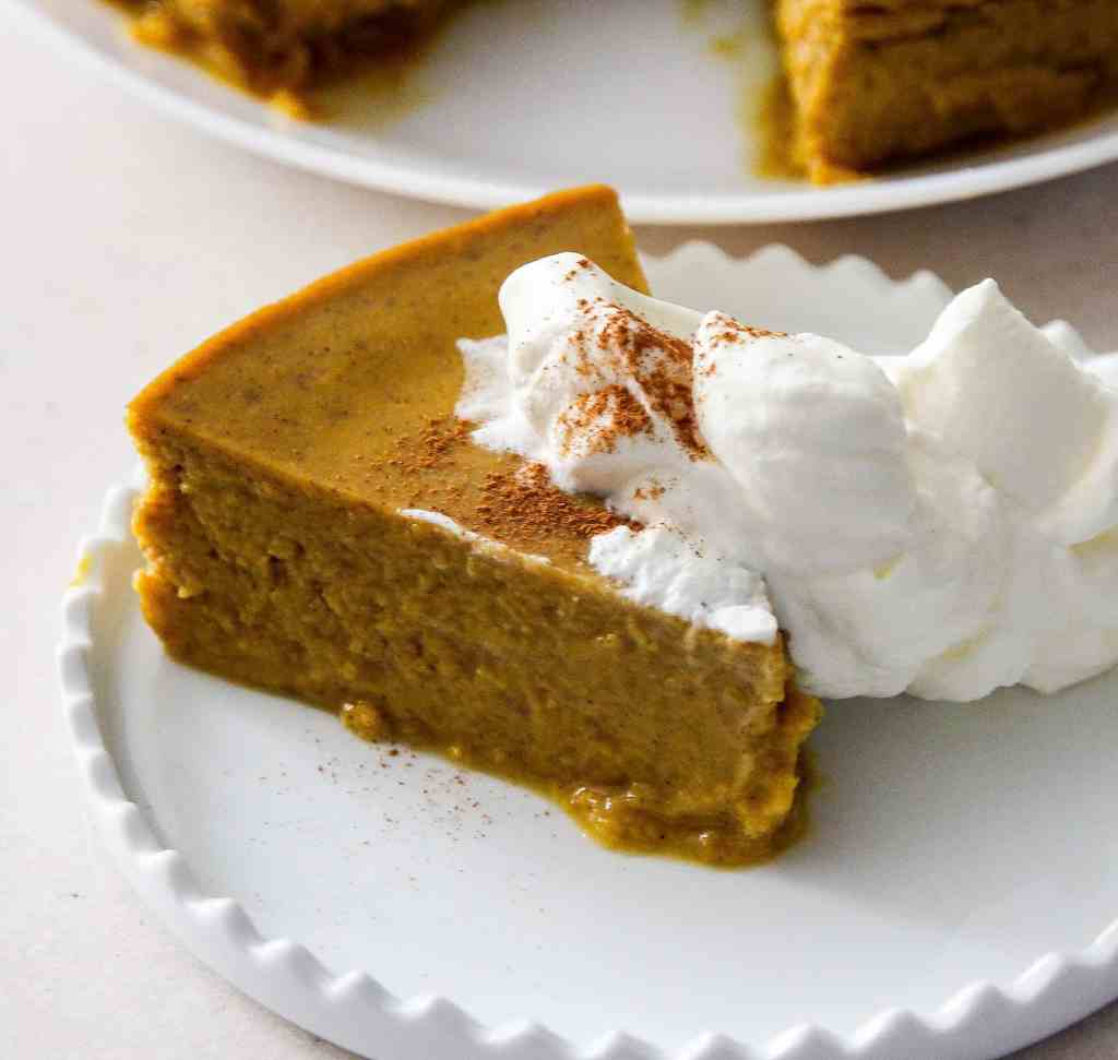 Sideways shot of a slice of crustless pumpkin pie. Perfect, crustless pumpkin pie pudding makes a lovely low carb pumpkin dessert in your Instant Pot or Pressure cooker. This is an easy dump and go dessert.