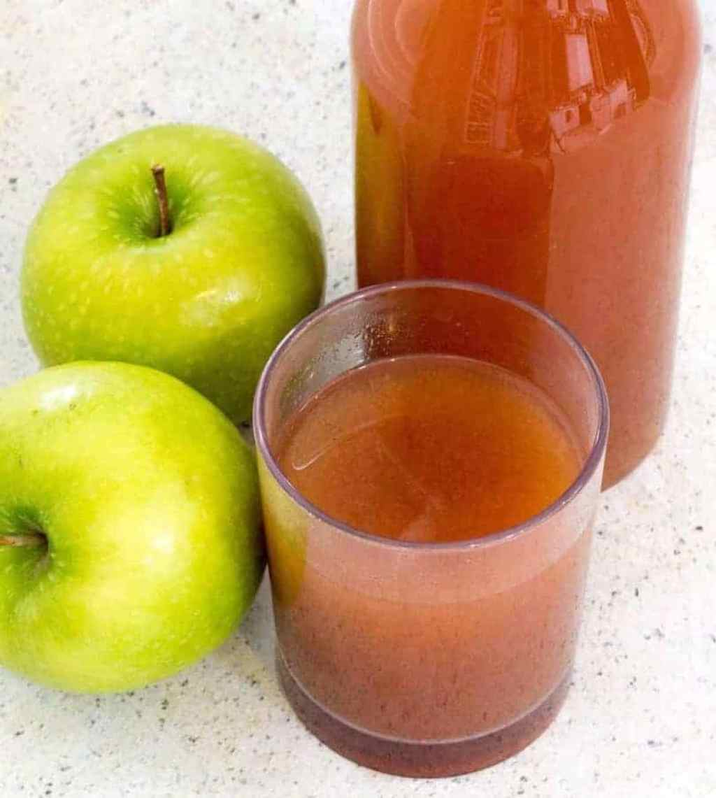 Glass of apple cider with two granny smith apples and a bottle of cider in the back. Here's how you can start with fresh apples, and end up with some of the most flavorful Instant Pot Mulled Apple Cider you've had—in about 30 minutes. Choose the sweetener and spices of your choice to customize this Mulled Apple cider to your taste.