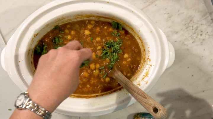 adding cilantro to ready chana masala