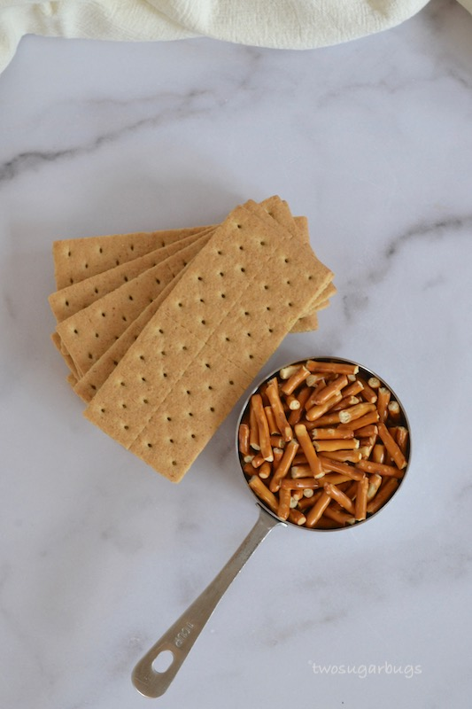 A stack of graham crackers and 1 cup of pretzels.