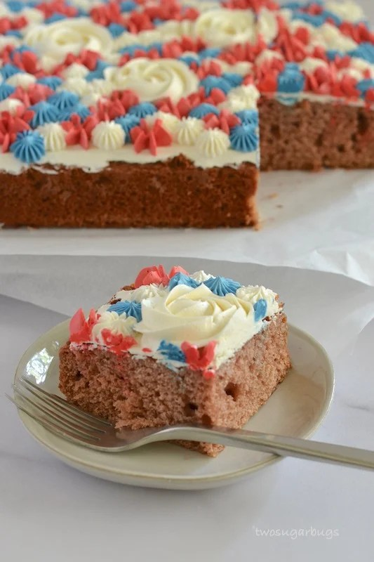 Slice of pink velvet cake on a plate with a fork