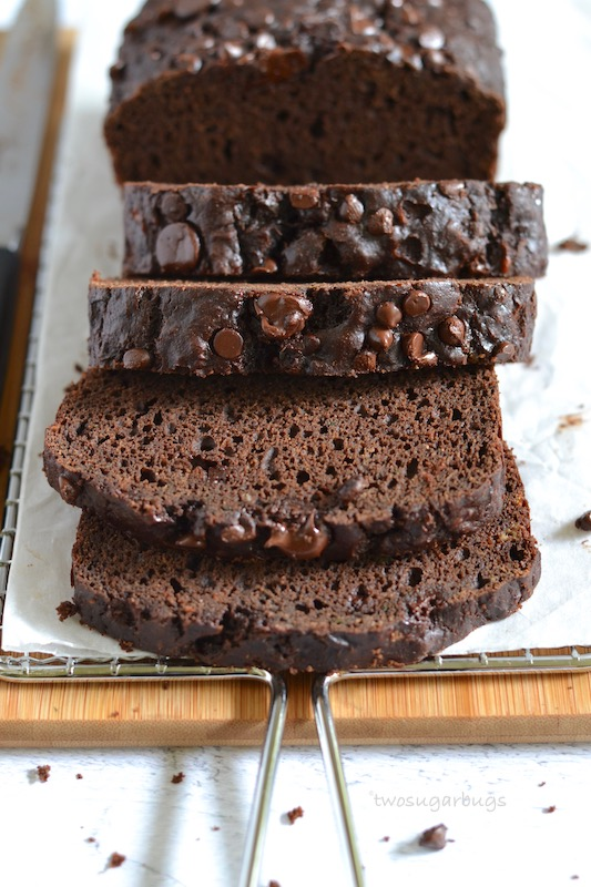 Slices of chocolate zucchini bread on a cutting board and cooling rack