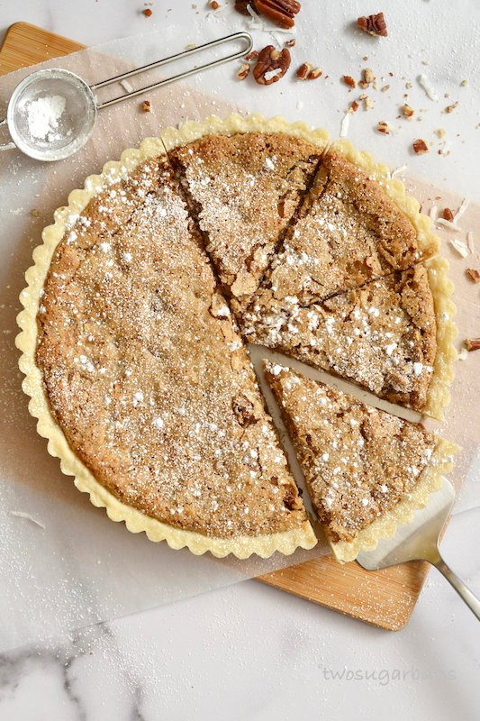Slice coconut pecan tart on a cutting board.