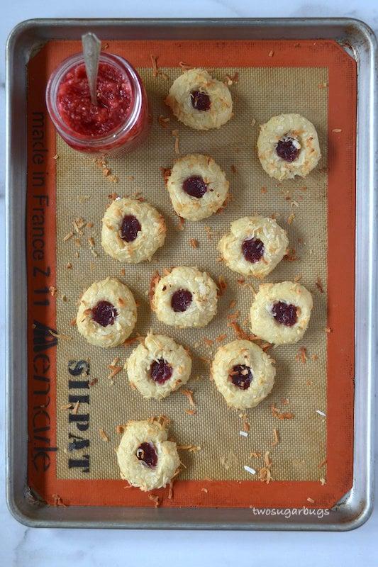 Baked coconut jam thumbprints on a baking mat
