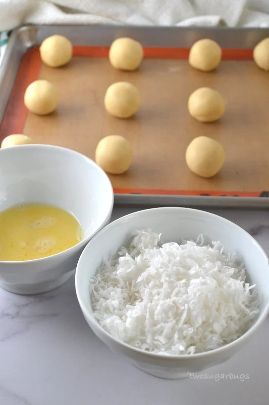 Coconut and egg wash in bowls with shortbread cookie dough balls