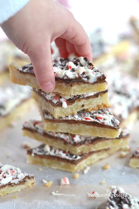 hand taking a cookie off the top of a stack of shortbread peppermint bark