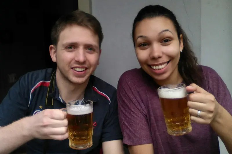 A man and a woman holding pint glasses with handles