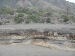 Faces carved into the sand on the way to Bromo