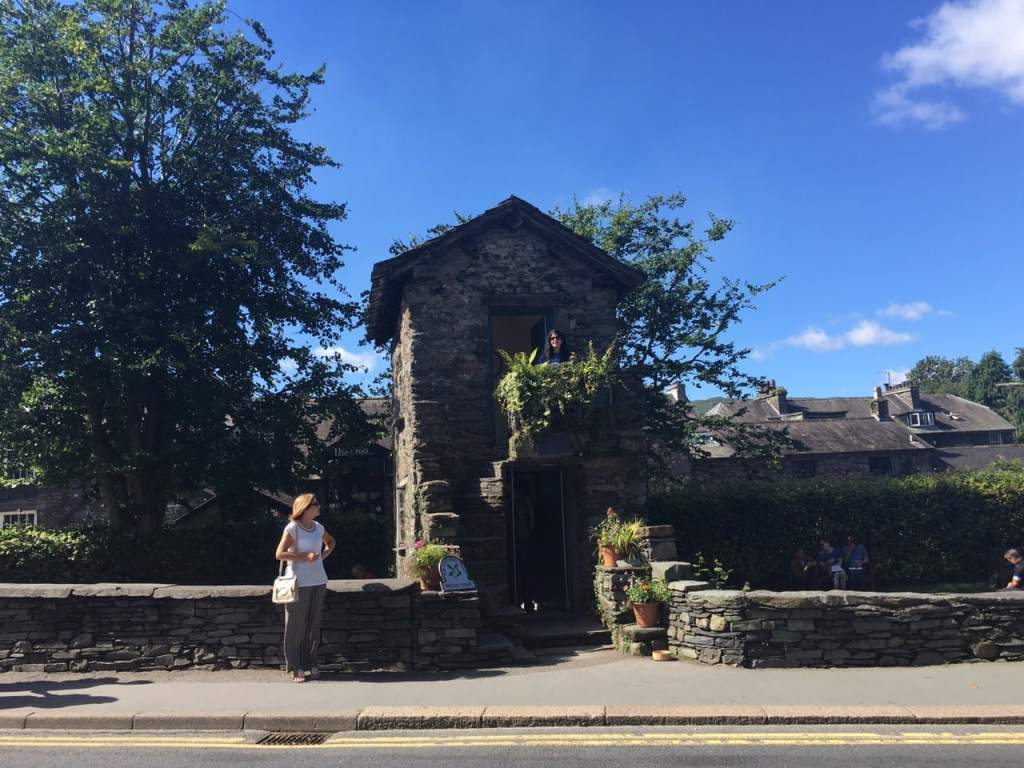 """Bridge House, Hard to tell from this angle but it is a small house over the river. Look closely and you see Anisa upstairs. - """"An Introduction to England's Lake District"""" - Two Traveling Texans"""