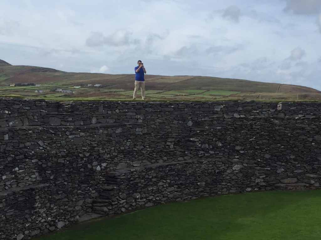 """Russell climbed the stone fort to get some pictures. - """"Why You Must Do the Ring of Kerry at Least Once in Your Lifetime"""" - Two Traveling Texans"""