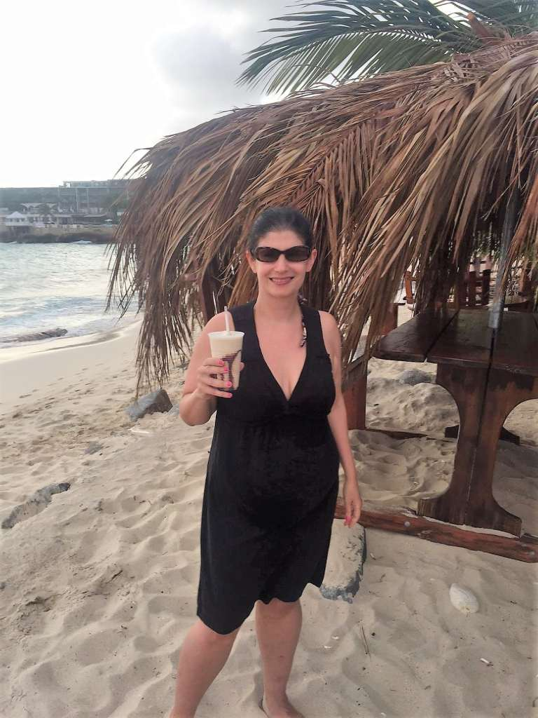 """Anisa enjoying a tropical drink at Guy's Driftwood Boat Bar. - """"Maho Bay: Plane Spotting in St. Maarten"""" - Two Traveling Texans"""