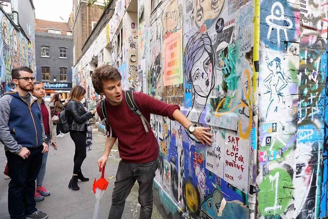 """Nathan shows us some of the smaller pieces of street art in the alley leading to the Star Yard. """"Free Shoreditch Street Art Tour"""" - Two Traveling Texans"""