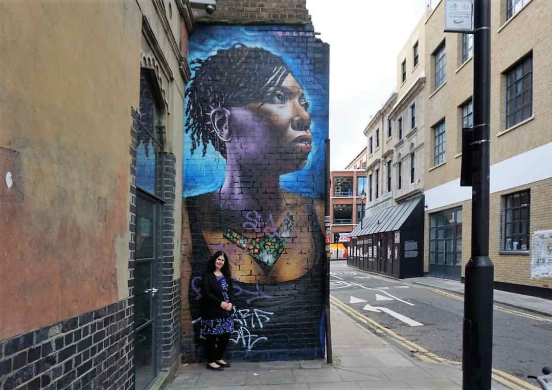 """Anisa with one of the portraits from Dreph's """"You are Enough"""" campaign. """"Free Shoreditch Street Art Tour"""" - Two Traveling Texans"""
