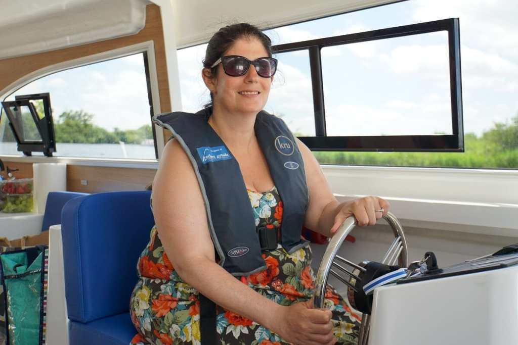 """Anisa driving the Broads boat! - """"Hire a Boat on the Norfolk Broads"""" - Two Traveling Texans"""