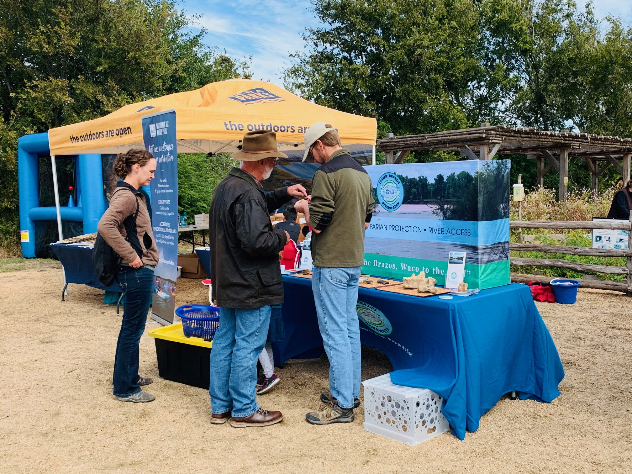 A photo showing people in front of the Lower Brazos River Watch booth.