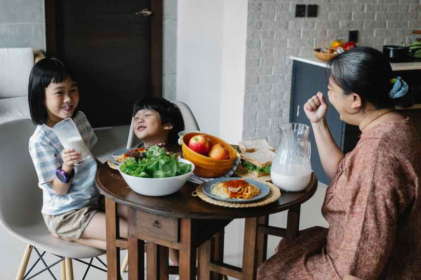 grandmother sitting at table with asian grandchildren