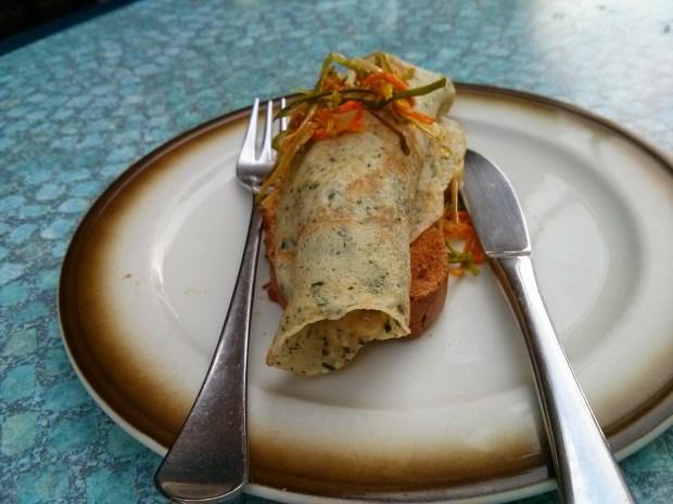 Naturaleza viva. Base de pan de maíz y pipas, crepe relleno de pollo al curry con verduras y tiras de crujiente de zanahoria y puerro.