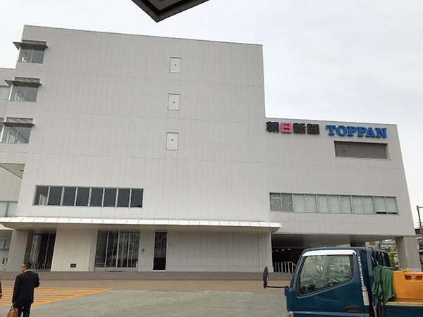 建物の壁面には「朝日新聞」と「凸版印刷」のロゴな並んで表記されています。