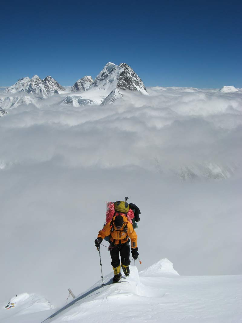 Chris Warner of Earth Treks indoor climbing gyms summitting a snowy mountain peak