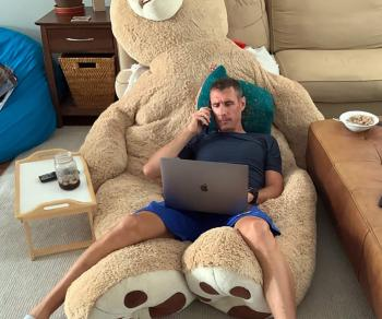 tyler lying on a stuffed bear for a remote office