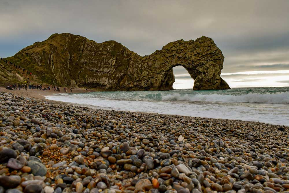 pebbled beach with durdle door in the background