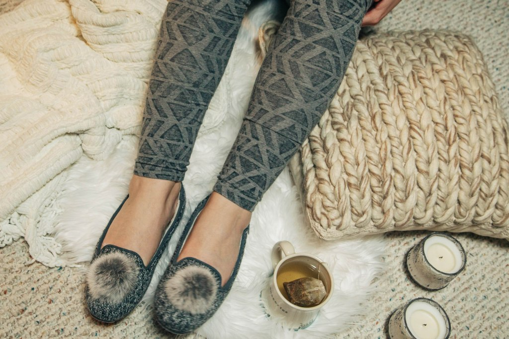 cozy woman's legs in leggings, pillows, blankets, cozy, tea, candles
