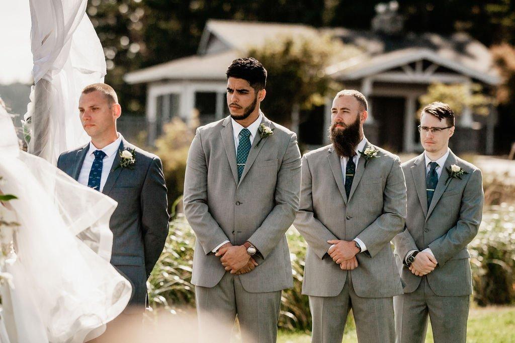 groom and goomsmen in suits at outdoor beach wedding