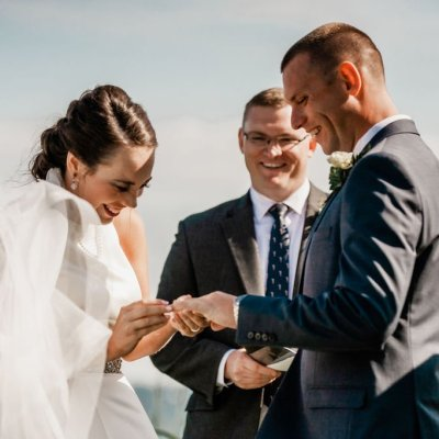 with this ring, bride putting ring on groom's finger at outdoor wedding ceremony