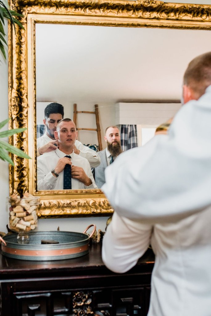 tying grooms tie, wedding day preparations, groom getting ready
